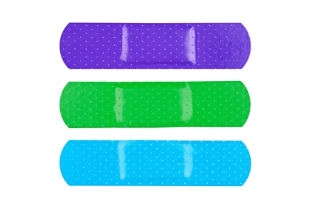 wound care: Three colorful adhesive bandages isolated on white