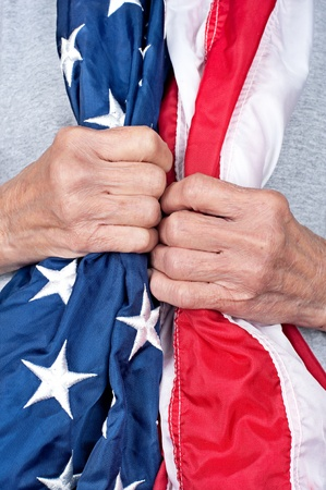 draped: An elderly partiotic woman clutching an American flag draped arounf her neck. Stock Photo