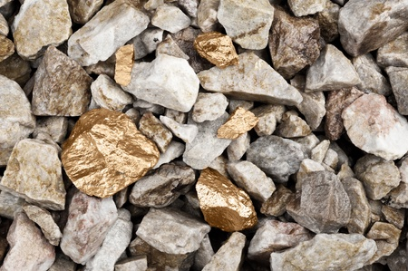 raw gold: Several golden nuggets in a rocky river bed.