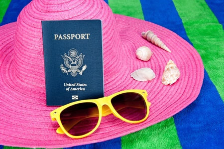 A passport on a pink tourist hat with yellow sunglasses and sea shells Stock Photo - 11199788