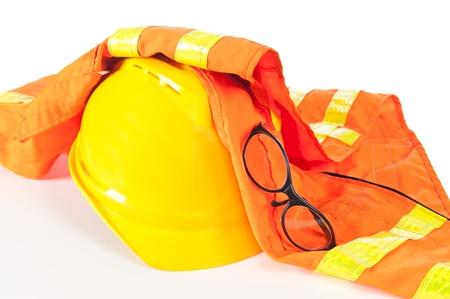 safety gear: Hard hat, reflective orange vest and safety glasses on white.