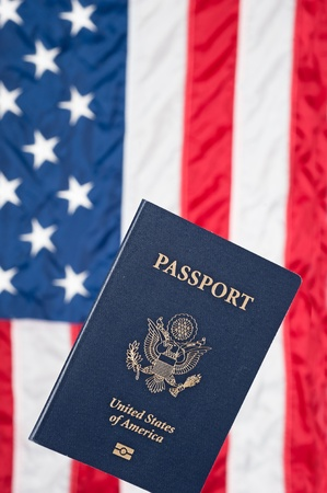 A USA passport with an American flag in the background photo