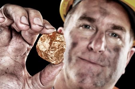 Un minero de oro muestra un Hugget de oro recién excavada de una mina.