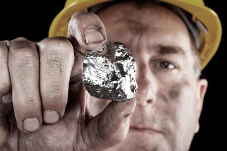 銀鉱山労働者彼の新しく掘られた銀のナゲットを披露します。