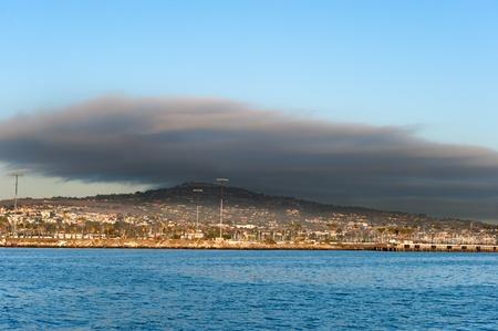 inclement: A dark cloud hangs over an upperscale community behind an oceanfront wharf.
