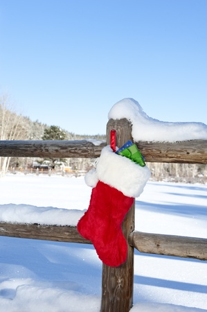 A Christmas stocking stuffed with presents hanging on a wooden fence in a wilderness resort mountain area. photo