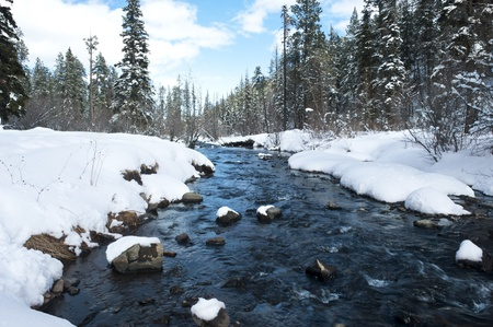 A river in the mountains with snow along the banks. photo