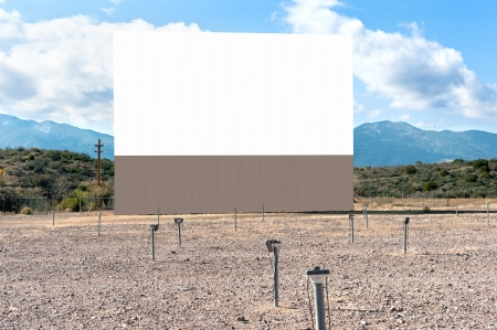 blank screen: An old and functional drive in theater with blank projection screen in a dessert setting and window speakers on posts for sound.