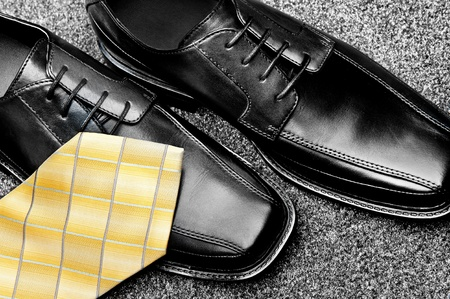 mens: A pair of black leather dress shoes with a yellow necktie Stock Photo