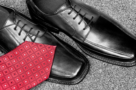 men's: A red necktie on a new pair of black leather dress shoes