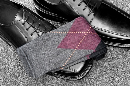 mens: A pair of black leather dress shoes with argyle socks Stock Photo