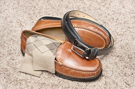 A new pair of tan leather shoes with socks and belt on beige carpet photo