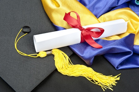 commencement: A graduation setting with cap,tassel, gown, hood and diploma.