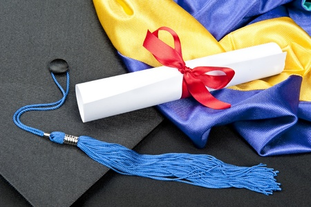 certification: A graduation setting with cap,tassel, gown, hood and diploma.