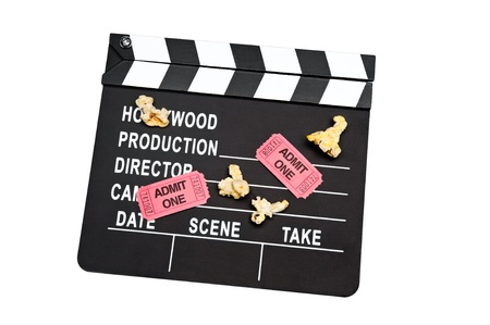 A film slate with movie tickets and popcorn on white photo
