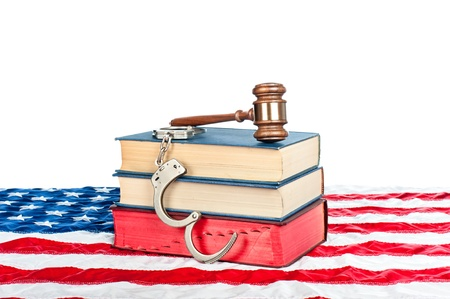 restraints: Gavel, law books and handcuffs resting on an American flag with a white background for placement of copy. Stock Photo