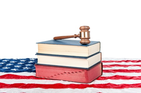 Gavel and law books resting on an American flag with a white background for placement of copy. photo