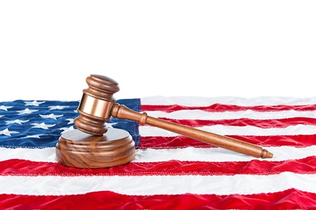 Gavel and sound block on an American flag with a white background for placement of copy.