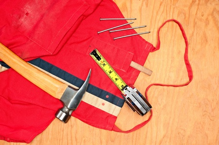 Woodworking tools including a hammer, tape measure, carpenter's pencil and old red apron on a piece of plywood plank