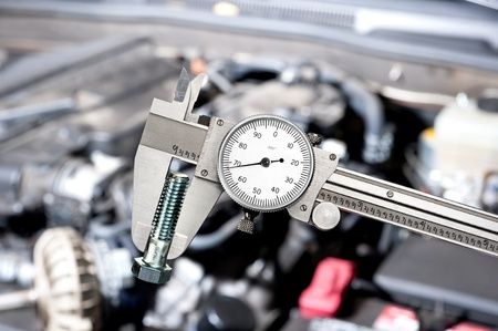 calipers: A shiny vernier caliper micrometer in front of a car engine during for servicing and repair Stock Photo