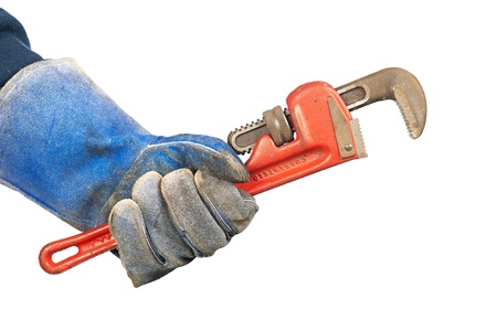 adjustable wrench: A man holding an old, rusty plumber's pipe wrench while wearing worn out workshop gloves. Stock Photo