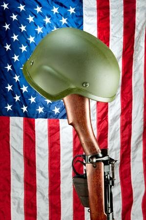 enfield: Un vecchio fucile Enfield seconda guerra mondiale con il casco contro una bandiera americana, un memoriale per i soldati americani caduti