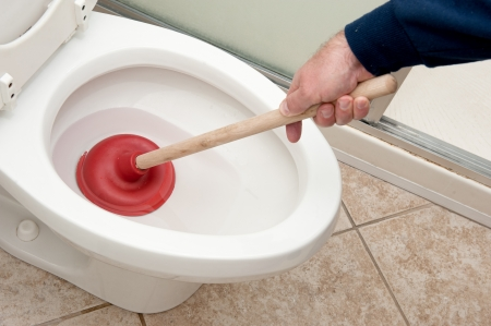 A plumber uses a plunger to unclog a toilet. photo