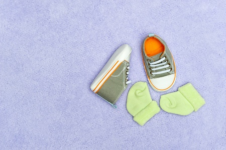 baby shoes: A pair of infant baby shoes and socks on a fluffy purple blanket.
