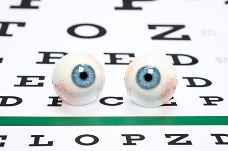 sight chart: A pair of prosthetic eyeballs on a snellen eye chart. Stock Photo