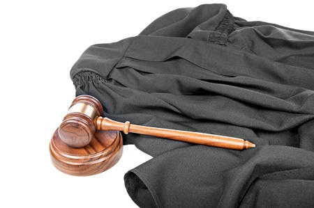 A judge's blaco gown and rich, wooden gavel with sound block on a white background photo