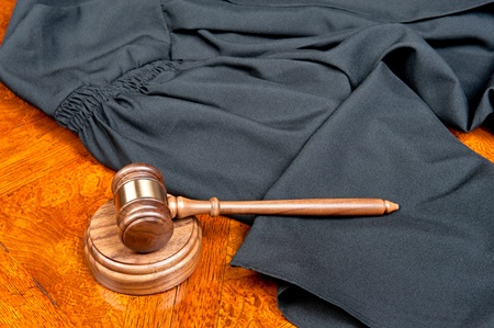 A judge gown and gavel with sound block on deep, rich colored wooden desktop photo