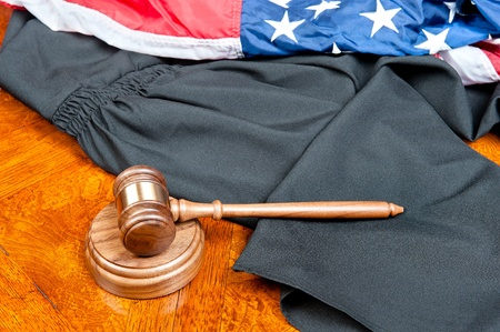A judge's gown and gavel with sound block on deep, rich colored wooden desktop and American flag photo