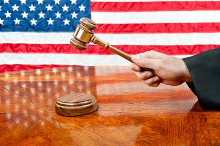 ruling: A judge's gown and gavel with sound block on deep, rich colored wooden desktop and American flag