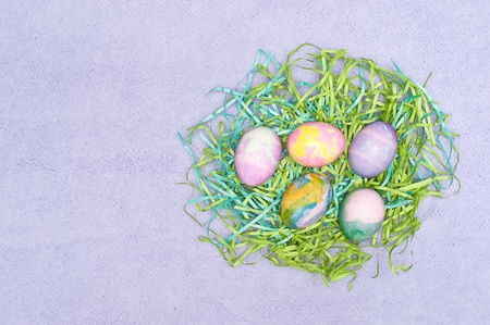 two and two thirds: Decorated Easter eggs on purple cloth   Image was composed using rule of the thirds, the left two thirds of the image is left open for designer to place copy   Stock Photo