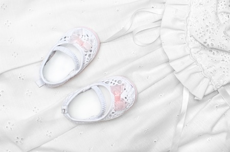 A new set of baby shoes on a white dress photo