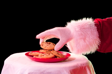 Santa Claus reaching for a fresh chocolate chip cookie from a red plate against a black background photo
