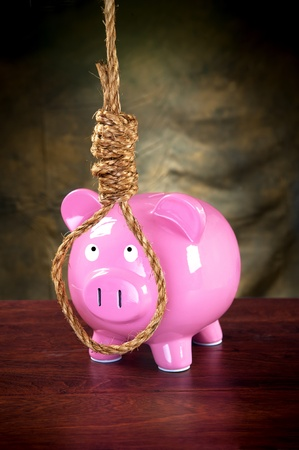 A pink piggybank against a dark, moody background prepared to hang himself with a noose. photo