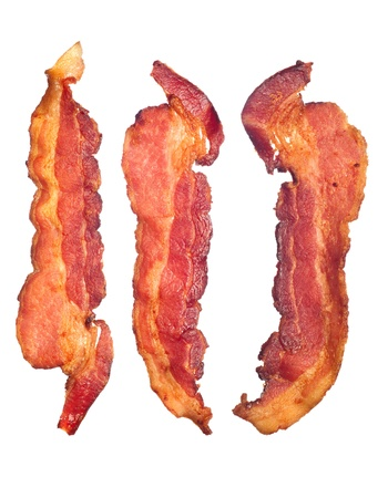 Three cooked, crispy fried bacon isolated on a white background.  Good for many health and cooking inferences. Foto de archivo