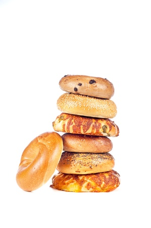 A stack of assorted, fresh, flavorful bagels on a white background. Bagels consist of onion, cheese, sesame, plain and blueberry. photo