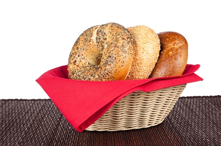 A wicker basket with three bagels including an onion bagel, sesame seed bagel and a wholegrain wheat bagel against a white background photo