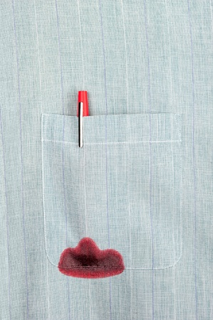 A red ink pen leaks in the pocket of a dress shirt.