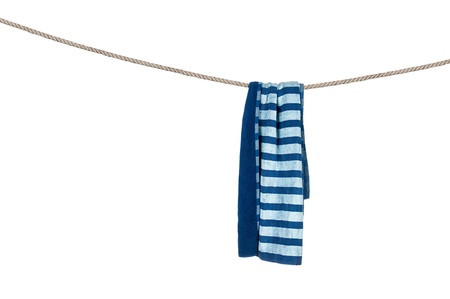 A beach towel hanging on a rope isolated on a white background.  For use as a design element or any inference for laundry, drying and summer fun.