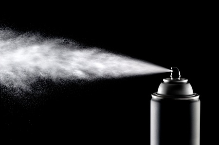 An aerosol can of spray dispensing its content against a backlit black background.