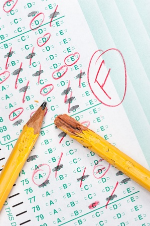 A graded test form with red scoring pencil marks indicates frustration and failure in the education system.  photo