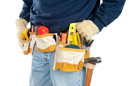 tools belt: A skilled tradesman stands with his fully loaded tool belt ready to work.  Isolated on white for designer convenience. Stock Photo