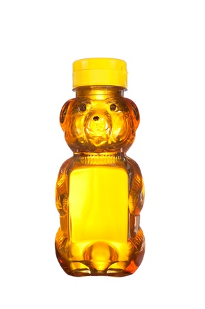 A fresh bottle of natural honey in a bear shaped container isolated on white Imagens