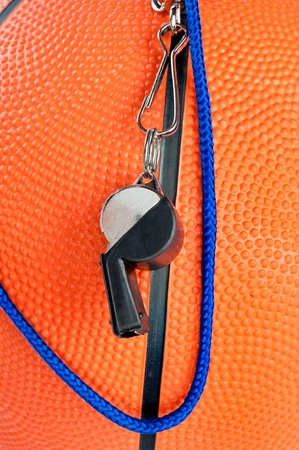 sound bite: A basketball referees whistle draped over an orange, rubber basketball. Good for sports inferences where rules are important. Stock Photo