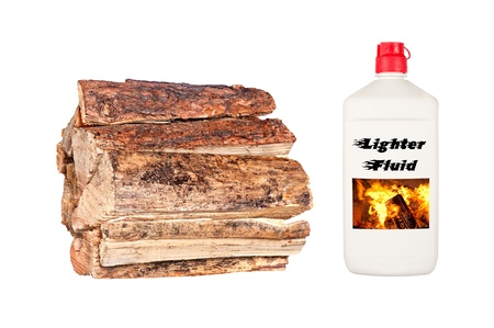 A stack of dry, fresh firewood isolated on white with a bottle of lighter fluid  photo