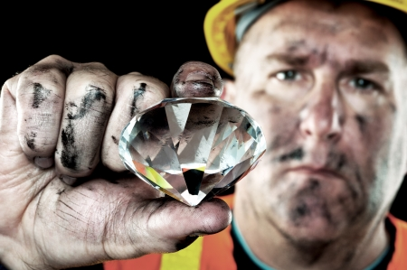 A dirty diamond miner covered in soot shows off a precious gem found in a coal mine. photo