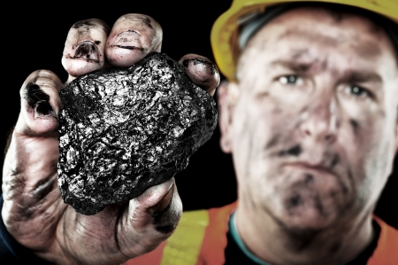 A dirty coalminer displays a lump of coal as a power and energy source. photo